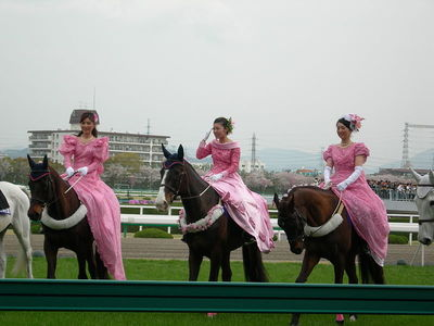 women in frocks, riding horses